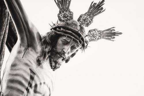 image: black and white image of a crucifix, close-up on Jesus' face