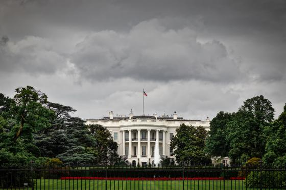 image of the White House with dark sky looming overhead