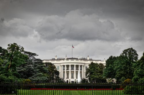 Image of white house in front of dark, ominous sky