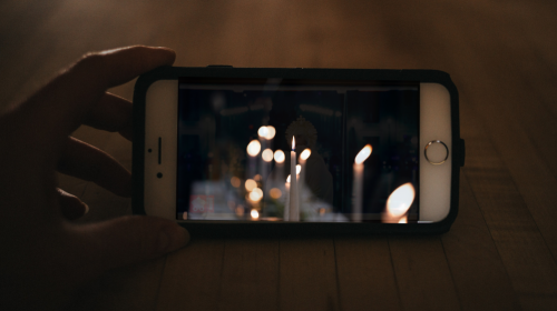 hand holding smartphone with candles on screen
