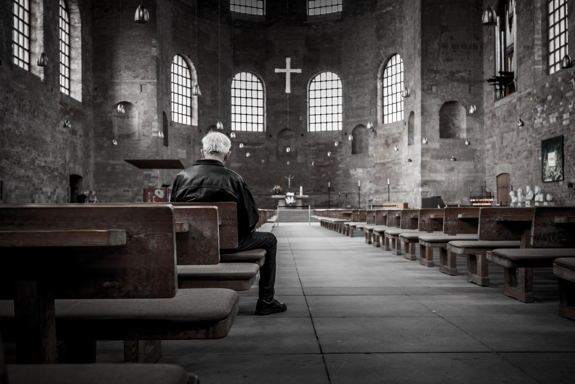 man with back to camera, sitting in a church pew