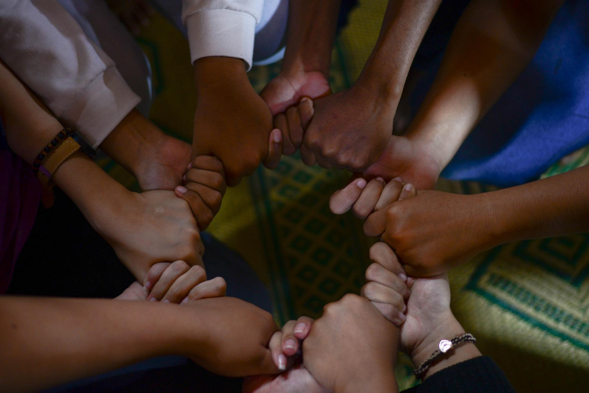 a circle of hands grasping one another