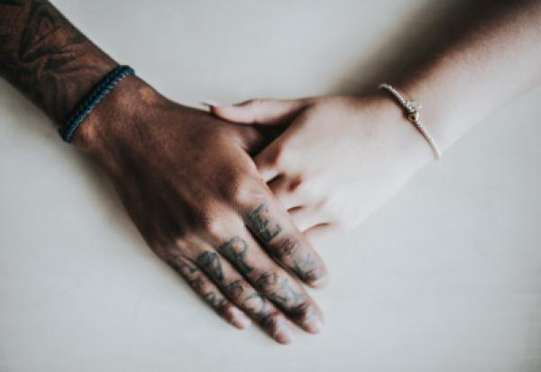 Two hands grasping one another, one black, one white