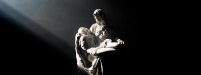A beam of light is cast upon a statue of the Pietà