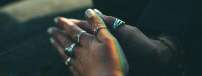 Black hands with rings in prayer position