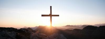 Cross on mountaintop in front of a sunrise
