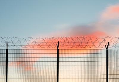 Barbed wire fence in front of blue and pink sky
