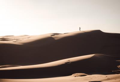 Desert sands with person standing on horizon