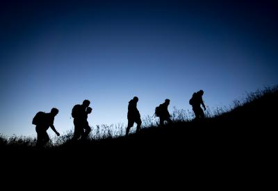 Silhouette of people climbing up a hill